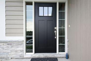 nex-gen windows and doors black front door with windows beside and brick and siding home
