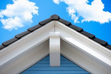 home roofing and siding with a bright cloudy sky in the background nex-gen windows and doors